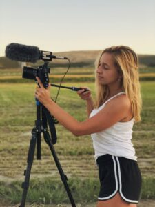 Madeline adjusts a video camera with a field in the background