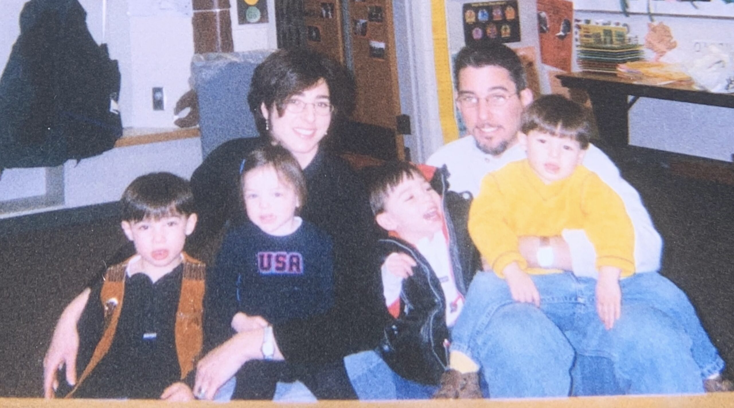 A grainy photo of two parents with four small children in their laps