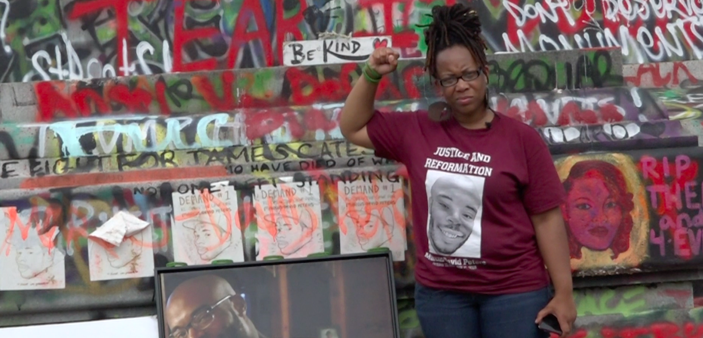 Woman stands in front of graffiti covered wall, raising her fist