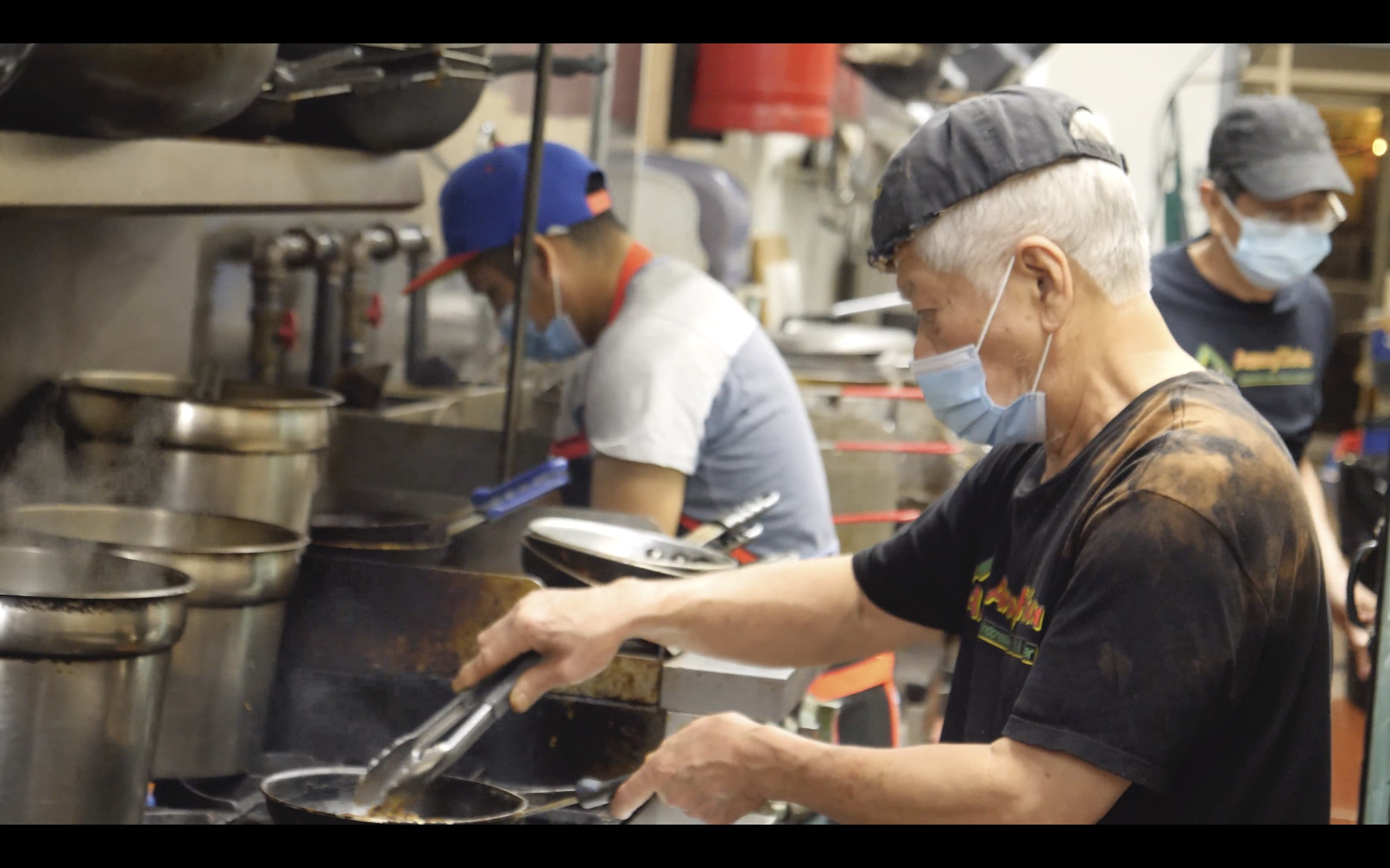 Man cooks in restaurant kitchen with mask on