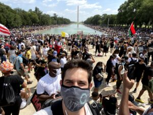 Victor takes a selfie with a mask on in front of a crowd of protesters in Washington DC