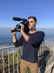 William stands in front of blue ocean, looking into a video camera